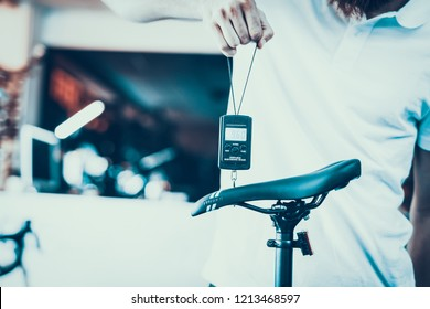 Guy Holds Portable Electronic Scale at Sport Shop. Closeup of Shop Assistant in White T-Shirt Measures and Shows to Camera Weight Details of Modern Black Saddle on Blurred Backround