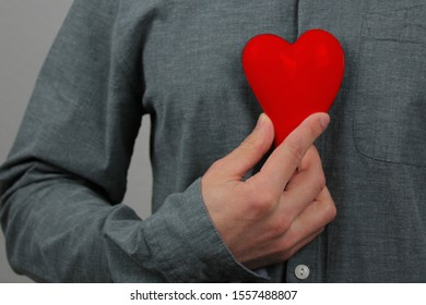 guy holds a red heart model in his hand in his hand, as a symbol of a declaration of love, concept of a declaration of love, marriage proposal, Valentine's Day, close-up