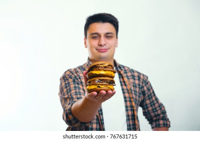 guy holds two burgers with one hand