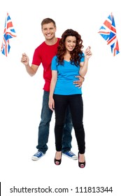 Guy hugging his girlfriend and both holding UK flag isolated over white background