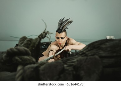 The guy in the image of an Indian with a Mohawk on his head sitting in the boat.