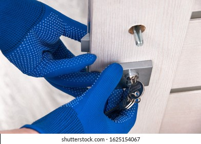 The guy installs new handles and a lock for the door to the room. Repair in the house. The guy in the blue gloves holds the door handles. Installing a door lock.