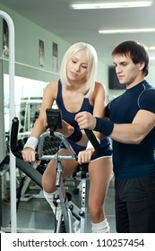guy instructor,  give instructions cutie girl, about execute exercise on exercise-bicycle, in  sport-hall