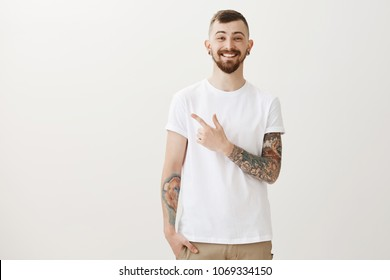 Guy introducing best friend to girlfriend. Portrait of pleasant joyful bearded male student in casual t-shirt with tattooed arms, pointing at upper left corner and smiling broadly over gray background