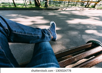 The guy in jeans and sneakers sits on a wooden bench in the park. First-person view