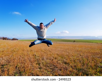 The guy jumps on a background of mountains and plants