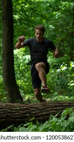 the guy jumps over a large log while participating in an ocr race