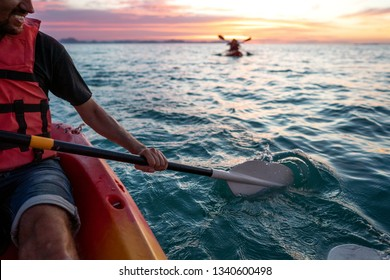 guy in kayaks in the sea at sunset
