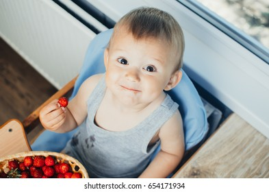the guy in the kitchen eating strawberries from the basket