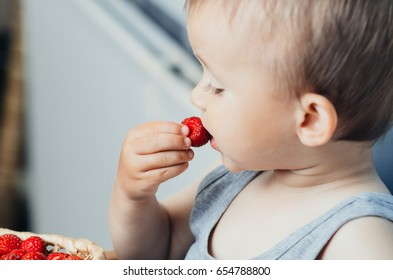 the guy in the kitchen eating strawberries from a basket