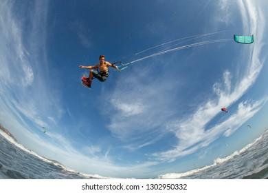 Guy Kitesurfing among waves
