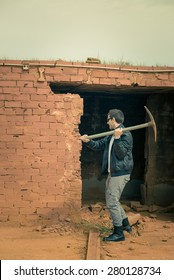 Guy knocking down a wall using a pickaxe