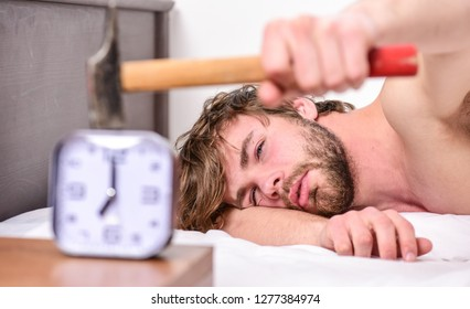 Guy knocking with hammer alarm clock ringing. Break discipline regime. Annoying sound. Stop ringing. Annoying ringing alarm clock. Man bearded annoyed sleepy face lay pillow near alarm clock.