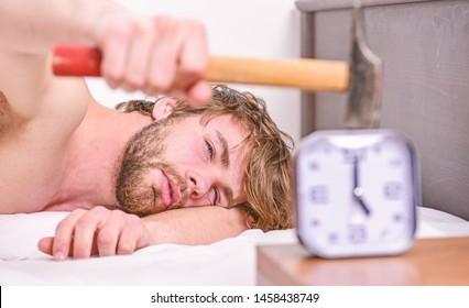 Guy knocking with hammer alarm clock ringing. Break discipline regime. Annoying sound. Stop ringing. Annoying ringing alarm clock. Man bearded annoyed sleepy face lay pillow near alarm clock.