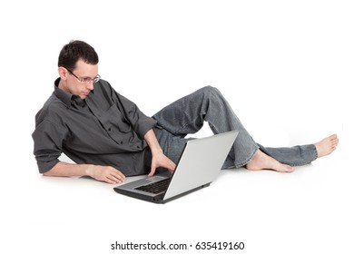 A guy with the laptop is liying on the floor isolated on a white background