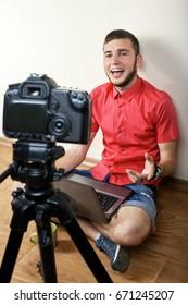 A guy with a laptop sits on the floor in front of the camera on a neutral background. Concept videobloger