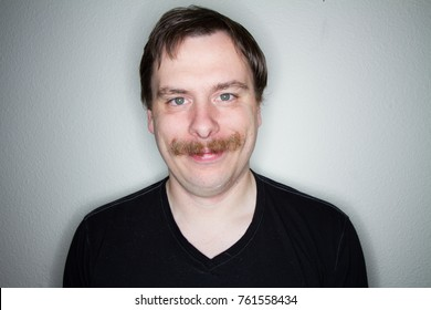 guy with a large mustache smiling