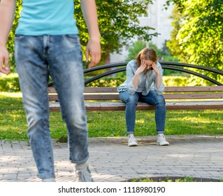 The guy leaves the young girl. This park is in nature. A girl is sad and crying is sitting on a bench. The concept of the problem in the family and breaking the relationship.
