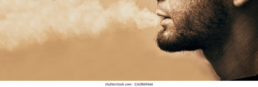 guy lets out the cigarette smoke, stop smoking. vape. copy space. board