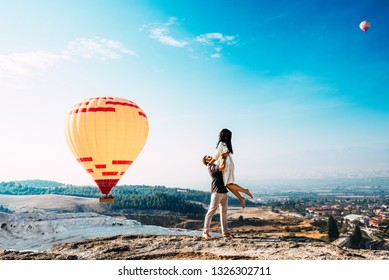 The guy lifted the girl on hands. Couple in love among balloons. Couple in love in Pamukkale. Couple in Turkey. Honeymoon trip. Man and woman traveling. Flying on balloons. Journey. Wedding travel