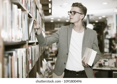 guy looking for interesting books on rack in bookshop