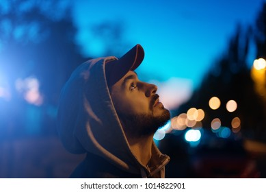 The guy looks at the evening sky.