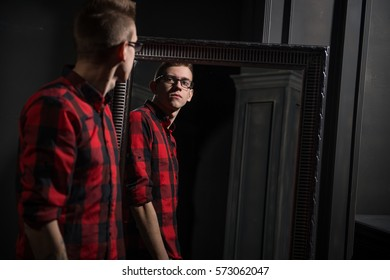 The guy looks in the mirror. Young handsome guy in the plaid shirt. Guy in the interior.