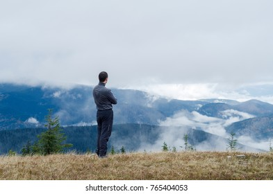 The guy looks at the mountains covered with clouds and fog