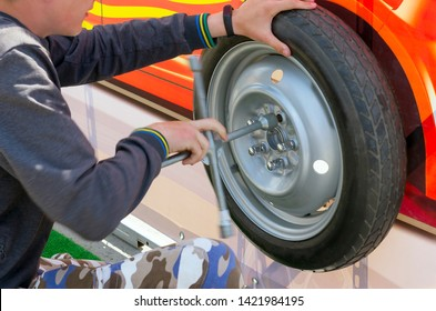 Guy Loosening the Wheel Lug Nuts with Wheel Spanner or Lug 4-Way Cross Wrench. Car Mechanic Training Stand.