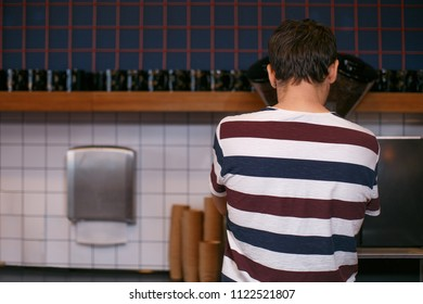 A guy makes coffee on a coffee machine, maybe he likes the place where he works, that he dressed in the color of the interior.