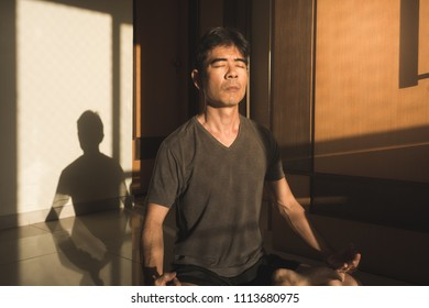 Guy meditating yoga lotus pose with eyes closed sitting on the floor at home - Morning routine - Silence, solitude and mindfulness concept