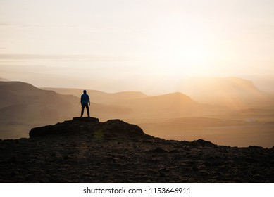 Guy meets the sunrise on the top of the mountain. Natural background with space for text