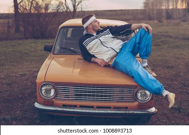 guy in the nineties lies on the hood of an old car