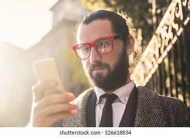 Guy on his phone with red glasses