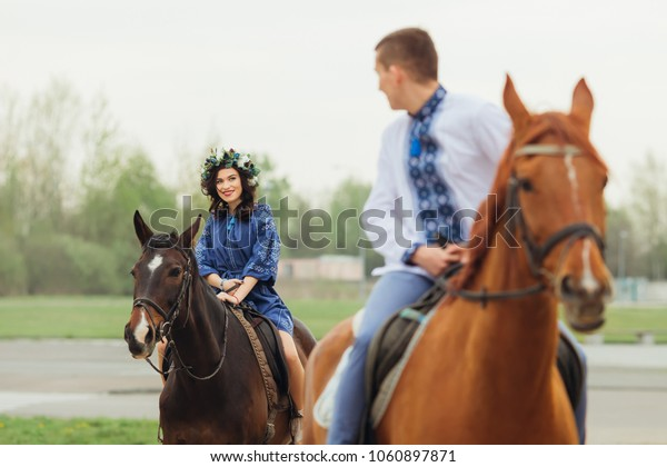 guy on a horse riding in front looking over his shoulder to his girlfriend who also rides on a horse