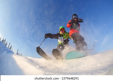 A guy on skis and a girl on a snowboard perform a trick against the background of a blue winter sky.