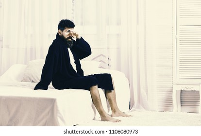 Guy on sleepy face getting up in morning. Macho with beard and mustache sluggish relaxing after nap, rest. Man in robe sits on bed, white curtains on background. Awakening concept.
