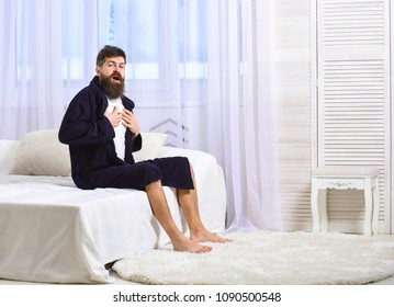 Guy on sleepy face yawning in morning. Awakening concept. Macho with beard and mustache sluggish yawning, relaxing after nap, rest. Man in robe sits on bed, white curtains on background
