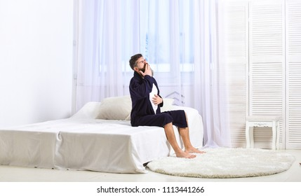 Guy on sleepy face yawning in morning. Awakening concept. Man in robe sits on bed, white curtains on background. Macho with beard and mustache sluggish getting up and yawning in morning.