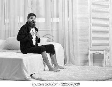 Guy on sleepy face yawning in morning. Awakening concept. Macho with beard and mustache sluggish yawning, relaxing after nap, rest. Man in robe sits on bed, white curtains on background.