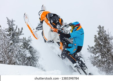 guy on a snowmobile jumping and flying into the misty mountain valley. on the background of white snow and snow-covered cedars. snowmobile freezing in the air