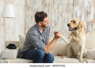 guy on the sofa holding paw of dog