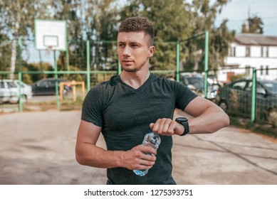 The guy opens a bottle of water. Outdoor activities after exercise. Athlete man holding a bottle of water.