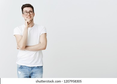 Guy overthinking feeling anxious and scared girlfriend find out he ate last chicken nugget. Nervous intense young man in glasses clenching teeth touching chin and holding at upper right corner worried