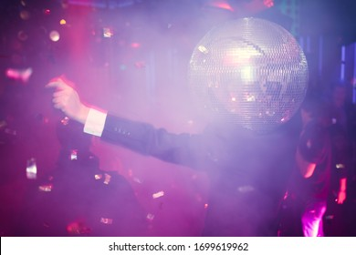 A guy at a party in a bright atmosphere with flying sweets in smoke in pink and blue lighting dancing with a disco ball on his head