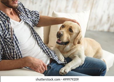guy petting his dog at home