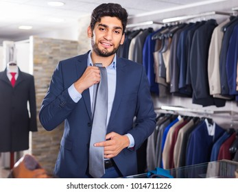 Guy is picking up tie for suit in men's shop.
