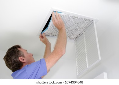 Guy placing into a square ceiling intake vent a clean white and blue air filter. As regular monthly maintenance a male puts in a new air filter in his ceiling air return.