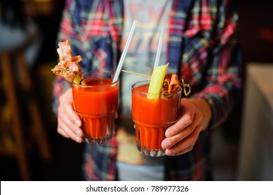 guy in the plaid shirt is holding two glasses of alcoholic cocktail Bloody Mary indoors