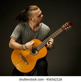 A guy playing an acoustic guitar. Dark background.